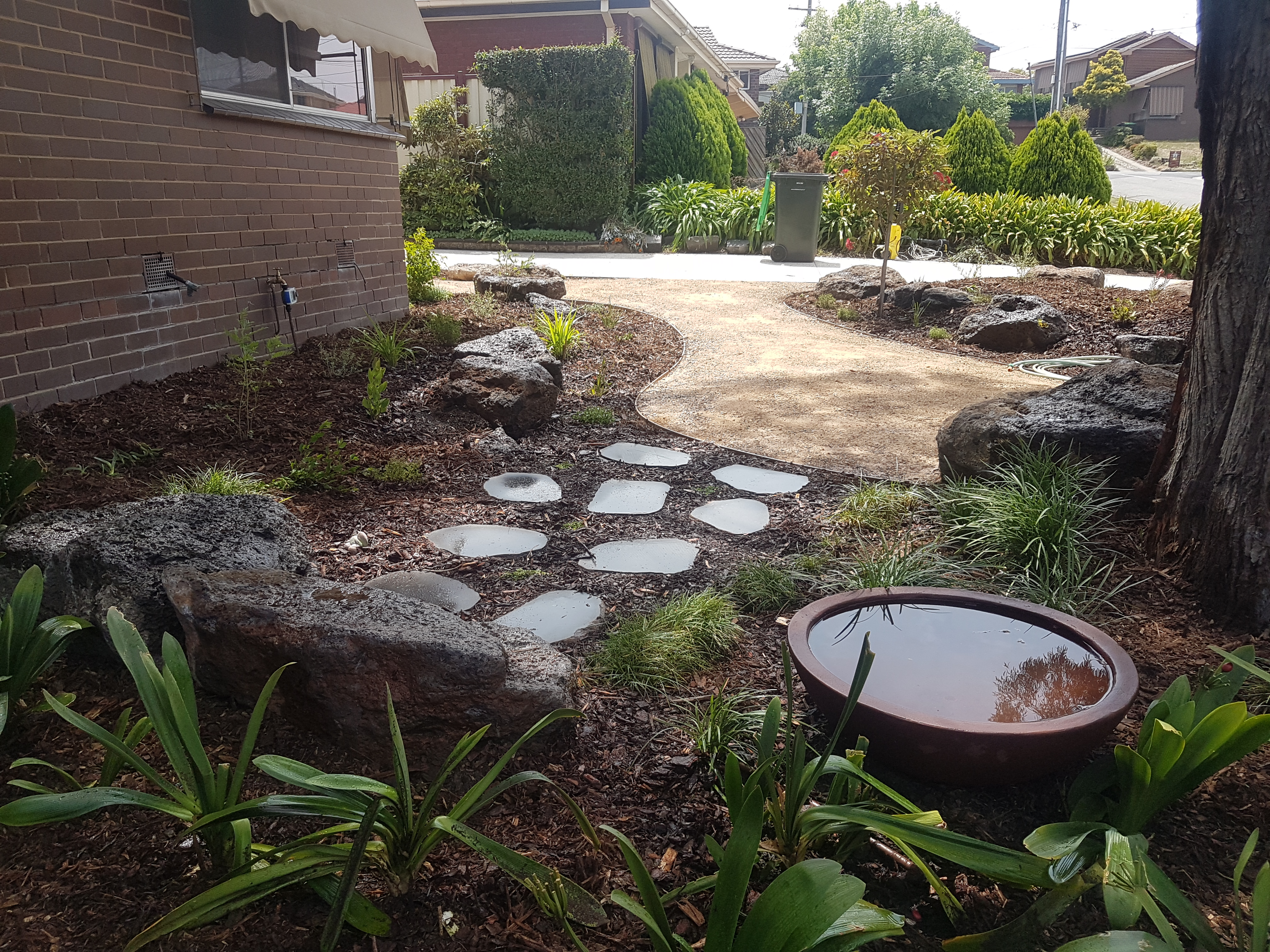 Rocks, stepping pavers, water bowl, shady garden