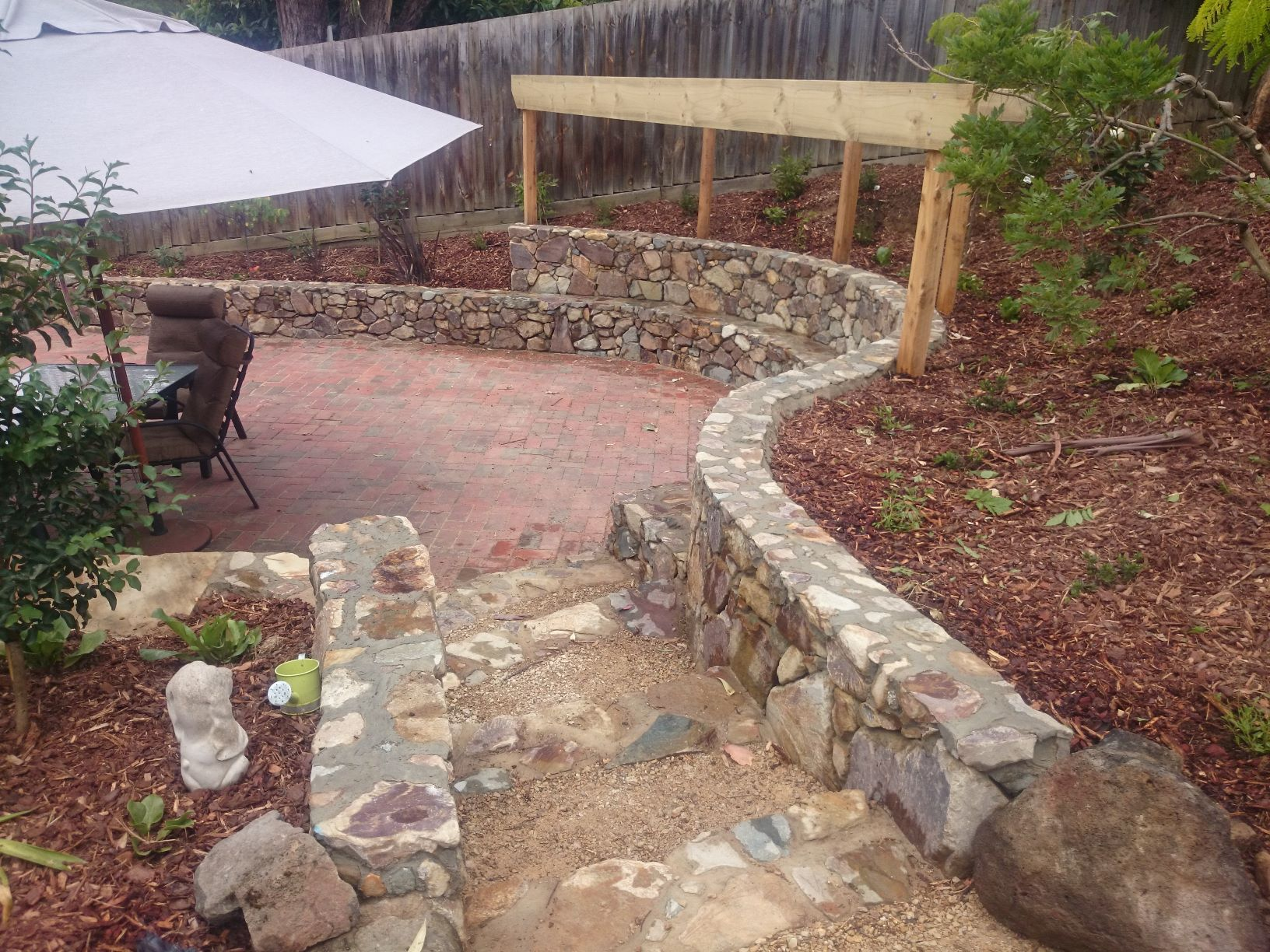 Coldstream Stone retaining wall with seat, Timber frame for climber, curved retaining wall, Eltham retaining wall, stone retaining wall, Eltham entertaining area