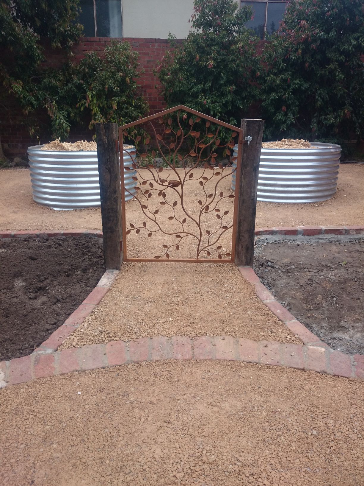 Country / Rustic style garden, Garden designed for kids, garden for chooks, veggie garden, Compacted Crushed sandstone, Corrigated Iron veggie beds, Up right railway sleepers, second hand red bricks, overwrought gate,