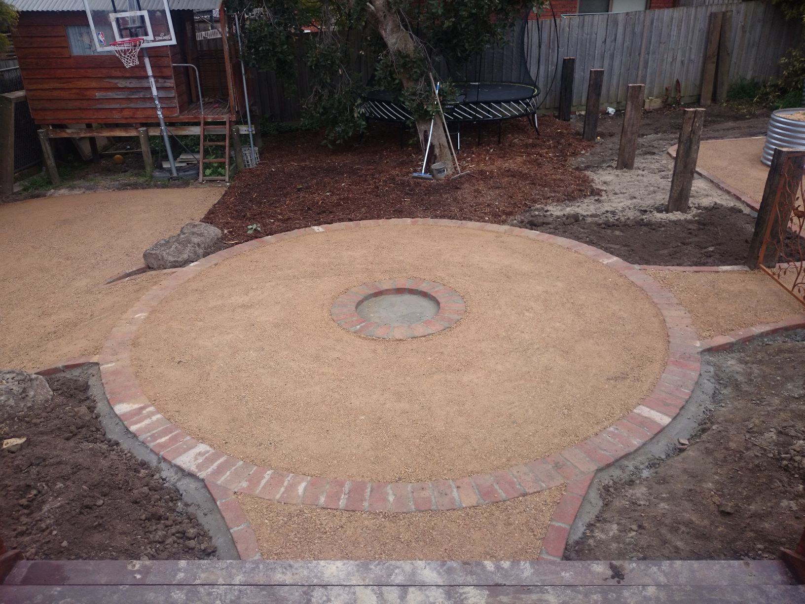 Country / Rustic style garden, Garden designed for kids, garden for chooks, veggie garden, Compacted Crushed sandstone, Corrigated Iron veggie beds, Up right railway sleepers, second hand red bricks, overwrought gate, Trampoline,