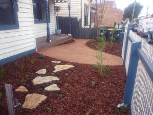 Native garden, compacted sandstone, path to the rubbish bins, Natural sandstone stepping pavers, natural privacy screen from the street.