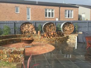 Fire wood stack, Coldstream seat, Bluestone, Second hand Red brick paving, Screening trees to block neighbours house,