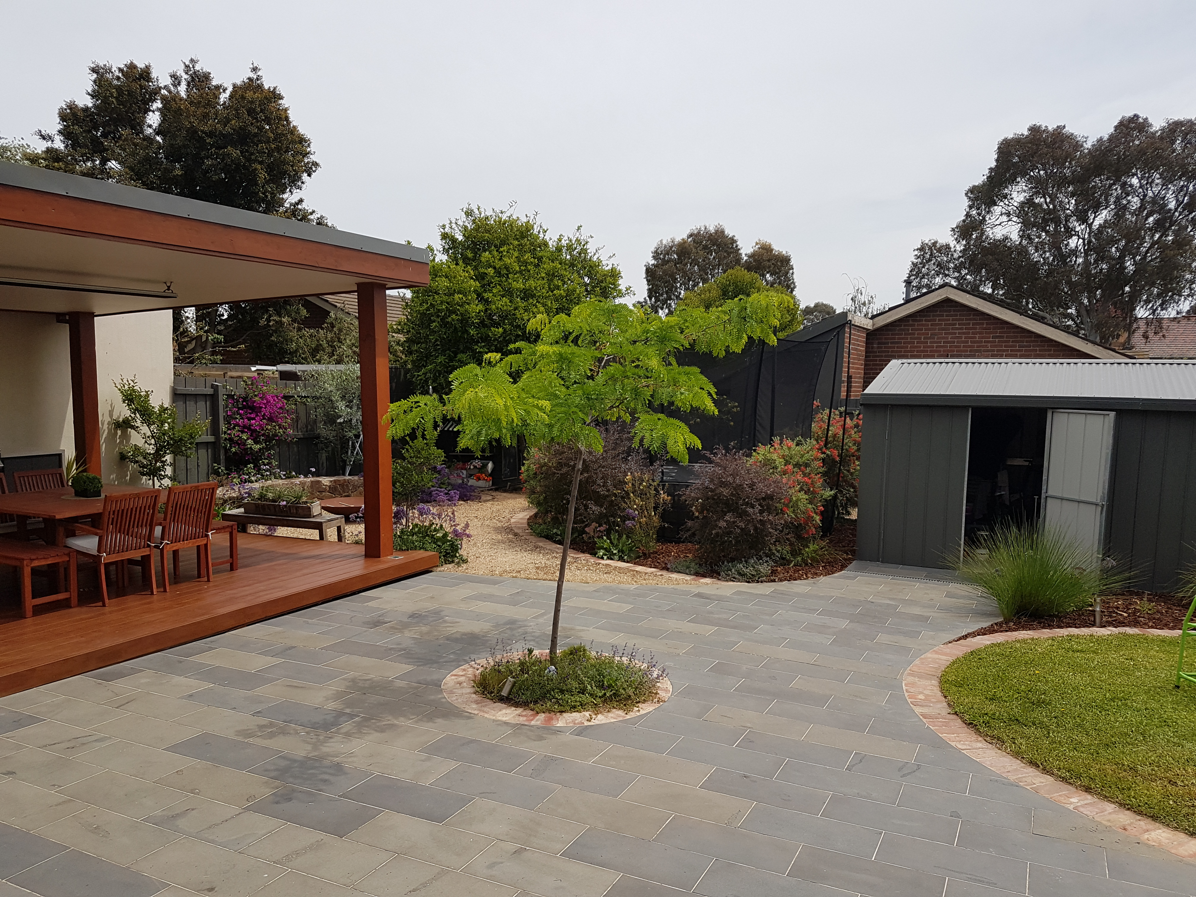 Bluestone paving, second hand red brick edging, shade tree in the centre, trampuline, large shed