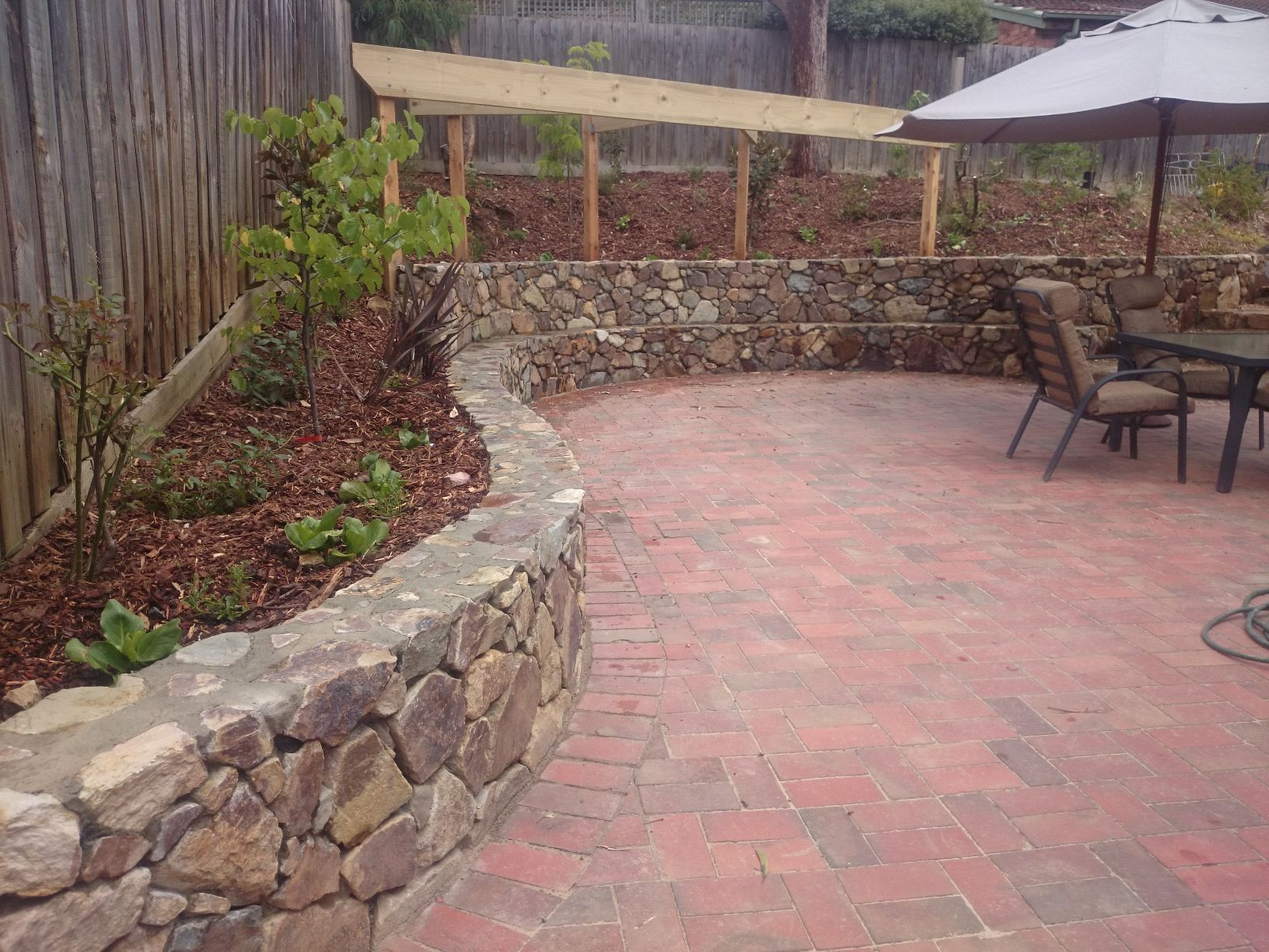 Coldstream Stone retaining wall with seat, Timber frame for climber, curved retaining wall, Eltham retaining wall, stone retaining wall, Eltham entertaining area.