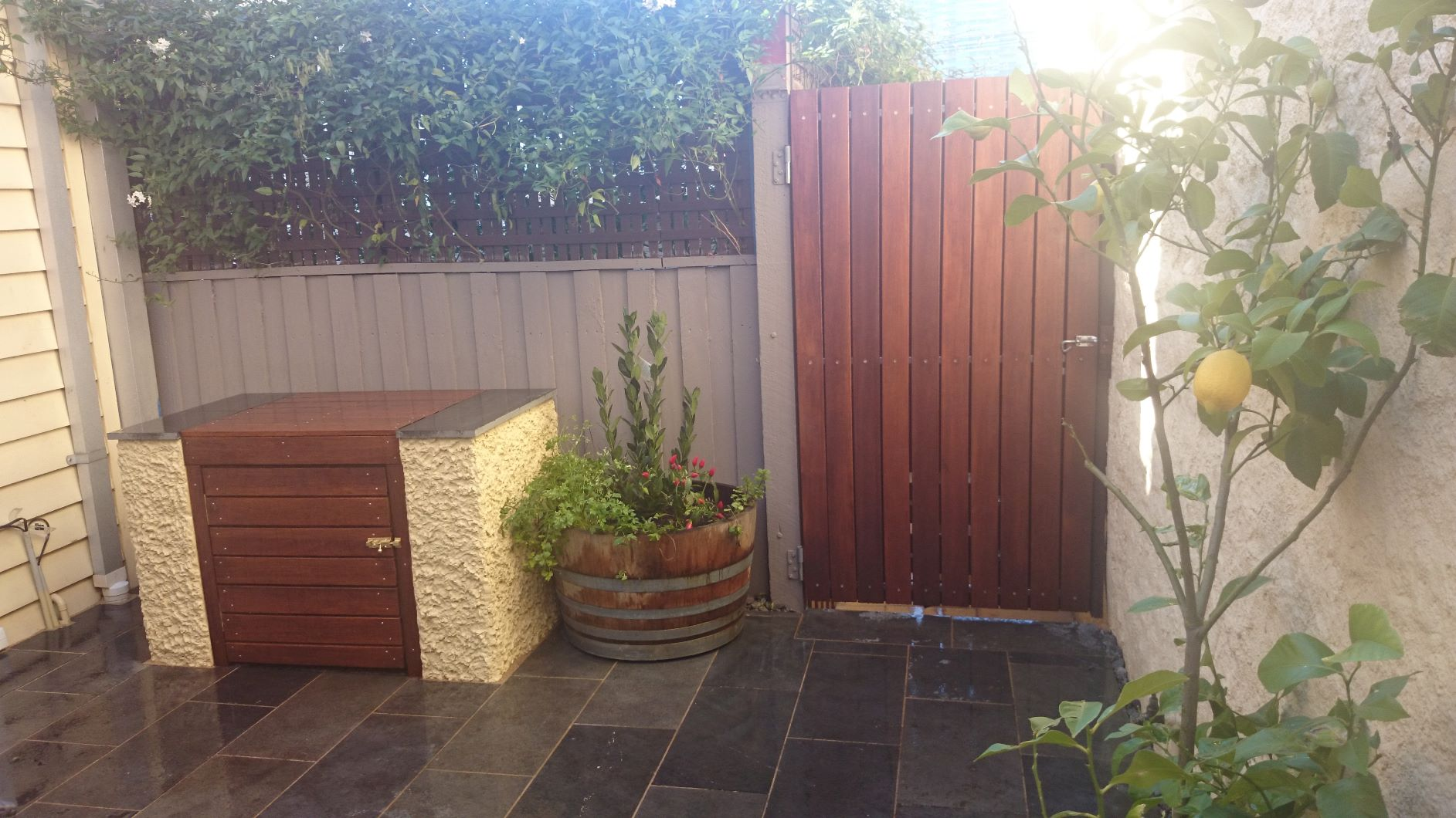 South Melbourne courtyard garden, Bluestone paving, rendered brick, Timber gate, BBQ bench..